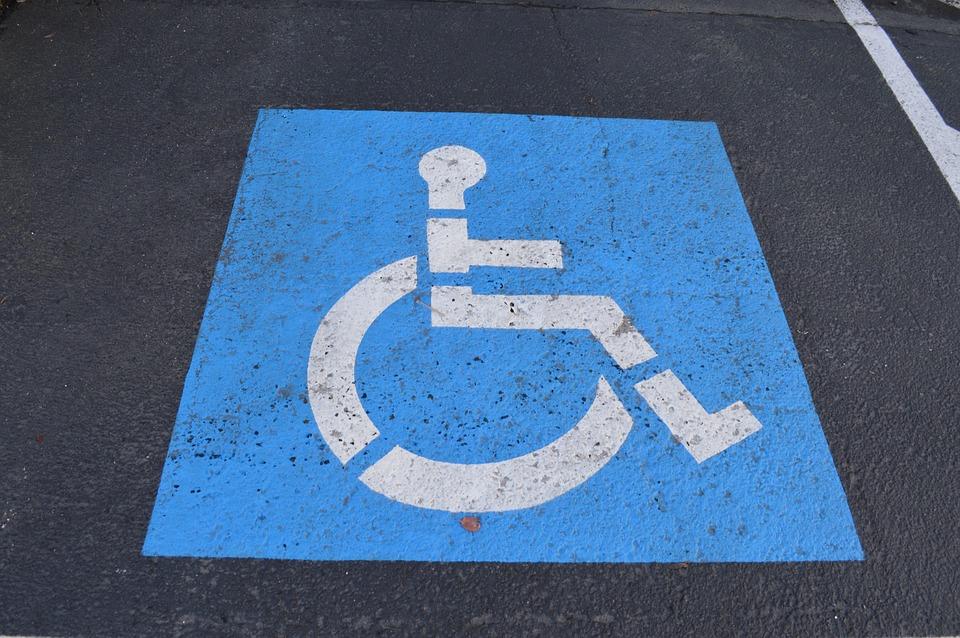 Photo prise d'un tarmac sur lequel il y a un symbole représentant une personne handicapée. Le symbole a un fond bleu avec une personne en chaise roulante, de profil, en blanc.