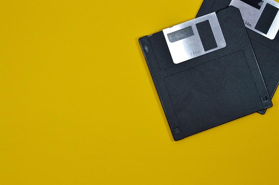 Photo prise de deux cartes mémoires superposées.Elles se trouvent sur la partie droite de la photo. Elles sont posées sur une table jaune.