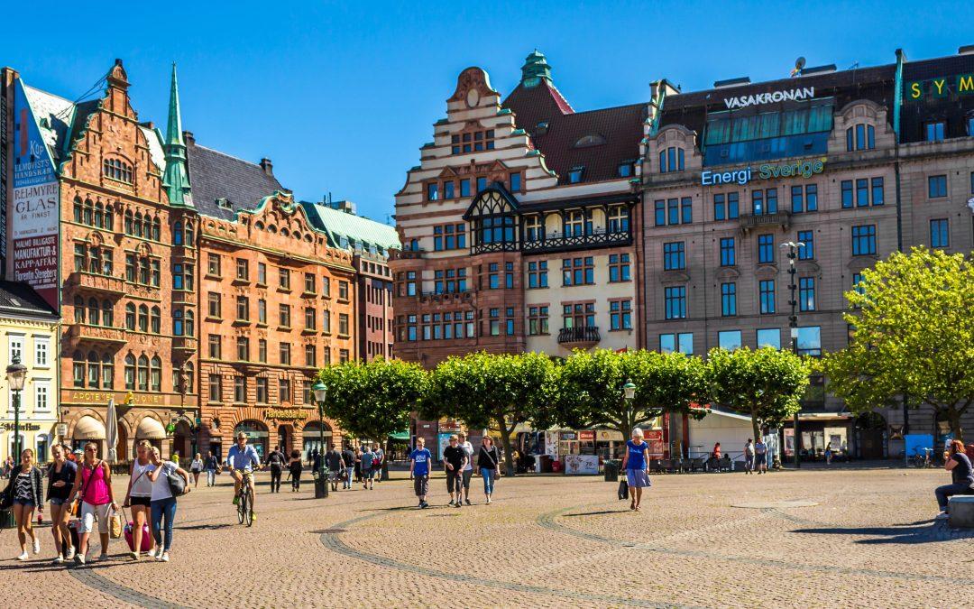 """Photo d'une place dans la ville de Malmo. Il y a des personnes qui marchent, qui roulent a vélo, et qui sont assises sur des marches. Autour de la place, des arbres et des batiments sur lesquelles il y a des inscriptions comme """"Vasakronan"""" ou """"Energi Sverige"""""""