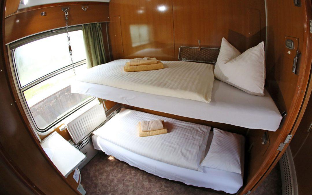 A l'intérieur d'un train de nuit, deux couchettes superposées sur lesquelles il y a un matelas avec par-dessus un oreiller, une couette et des serviettes de bain . Il y a un mur en bois vernis. A gauche, une fenêtre, un chauffage et une tablette.