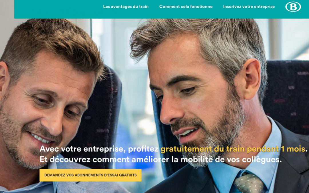 Image provenant de la SNCB sur laquelle deux hommes sont assis dans un train avec le sourire. Ils regardent dans la même direction. Il est écrit en blanc sur la partie inférieur de la photo : « Avec votre entreprise, profitez gratuitement du train pendant 1 mois. Et découvrez comment améliorer la mobilité de vos collègues. » Dans un encadrement jaune, il est écrit : « Demandez vos abonnements d'essai gratuits »